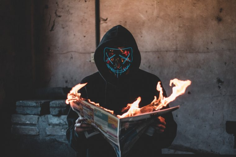 person holding a burning newspaper