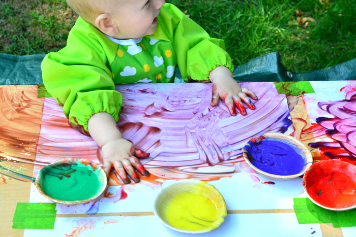 Baby playing with paint outside