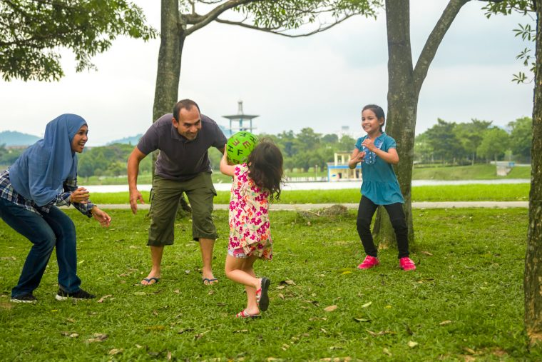 A family playing in a park, and little girl grab a ball and want to pass to her parent.