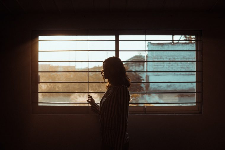 A woman looking out her window with sad lighting