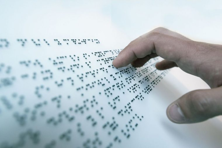 Hand of a blind person reading a text in the language of the blind, Braille.