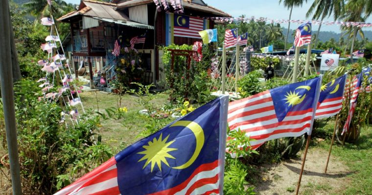 A house covered in jalur gemilang flags