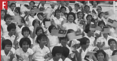 excited children waving the flag of Malaysia for the first time
