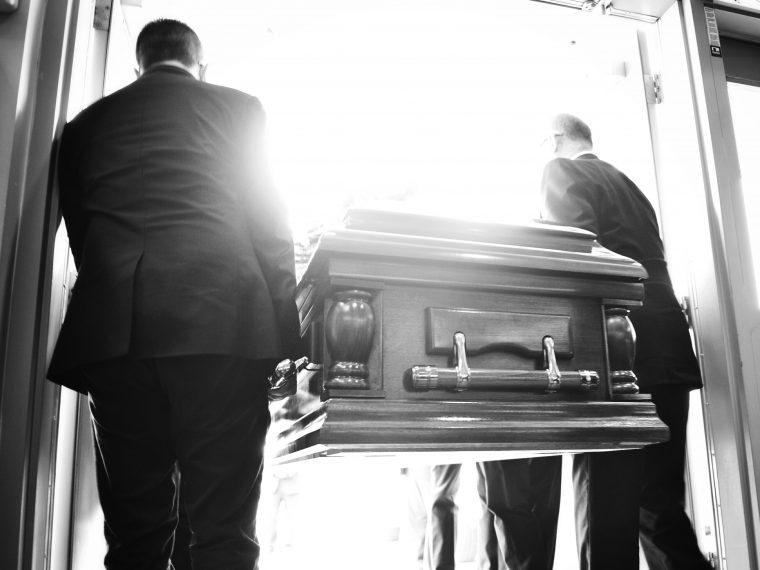 two men carrying a casket
