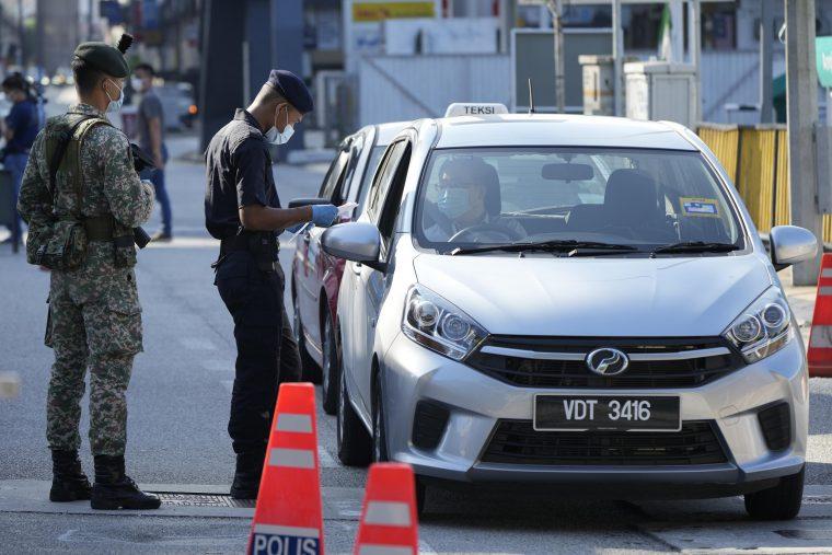 policeman at road block checking a driver's temperature