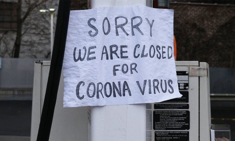"""A sign at a window saying """"Sorry We Are Closed For Corona Virus"""""""