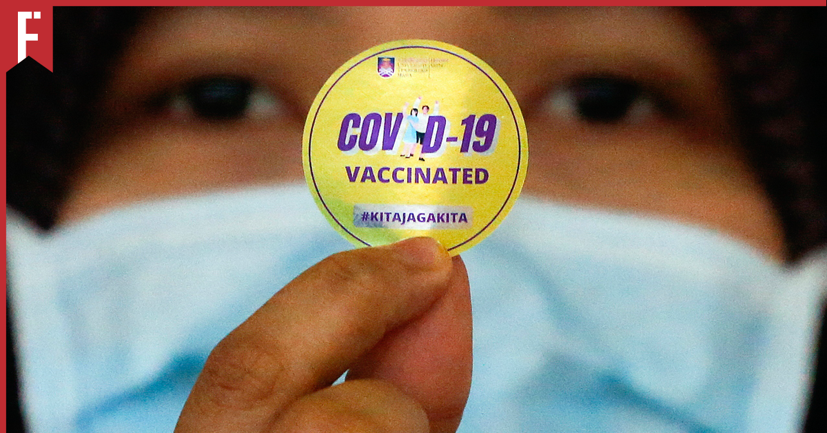fully vaccinated woman holding up a sticker as proof