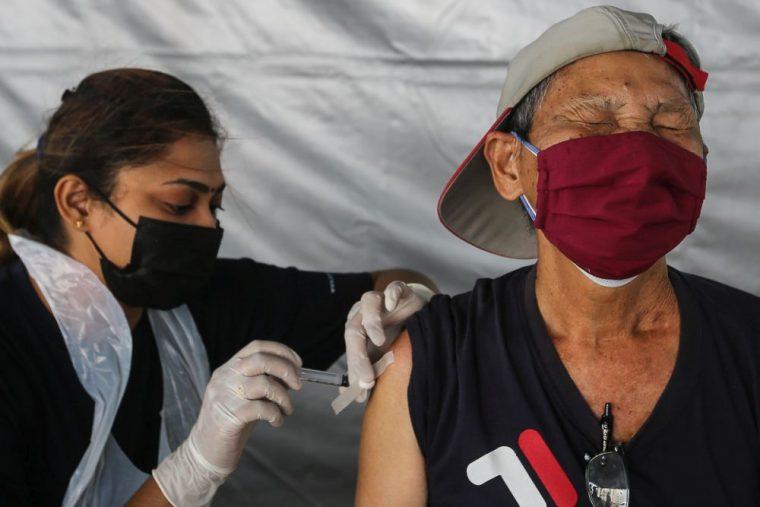 old man getting a vaccine jab in Malaysia