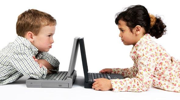 two children arguing over their laptops