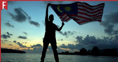 man raising jalur gemilang to celebrate malaysia day