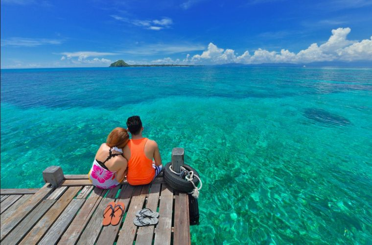 Malaysian couple relaxing on a jetty by the seashore