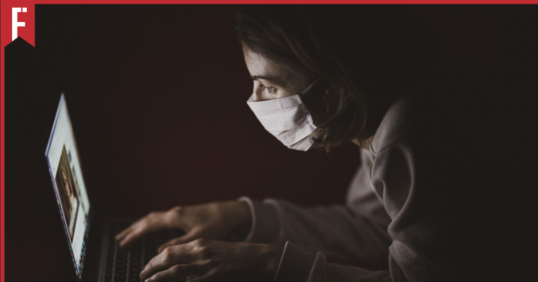 girl hunched over in the dark staring at a computer screen