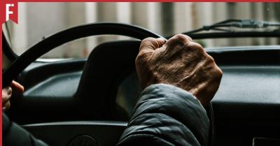 elderly man driving a car